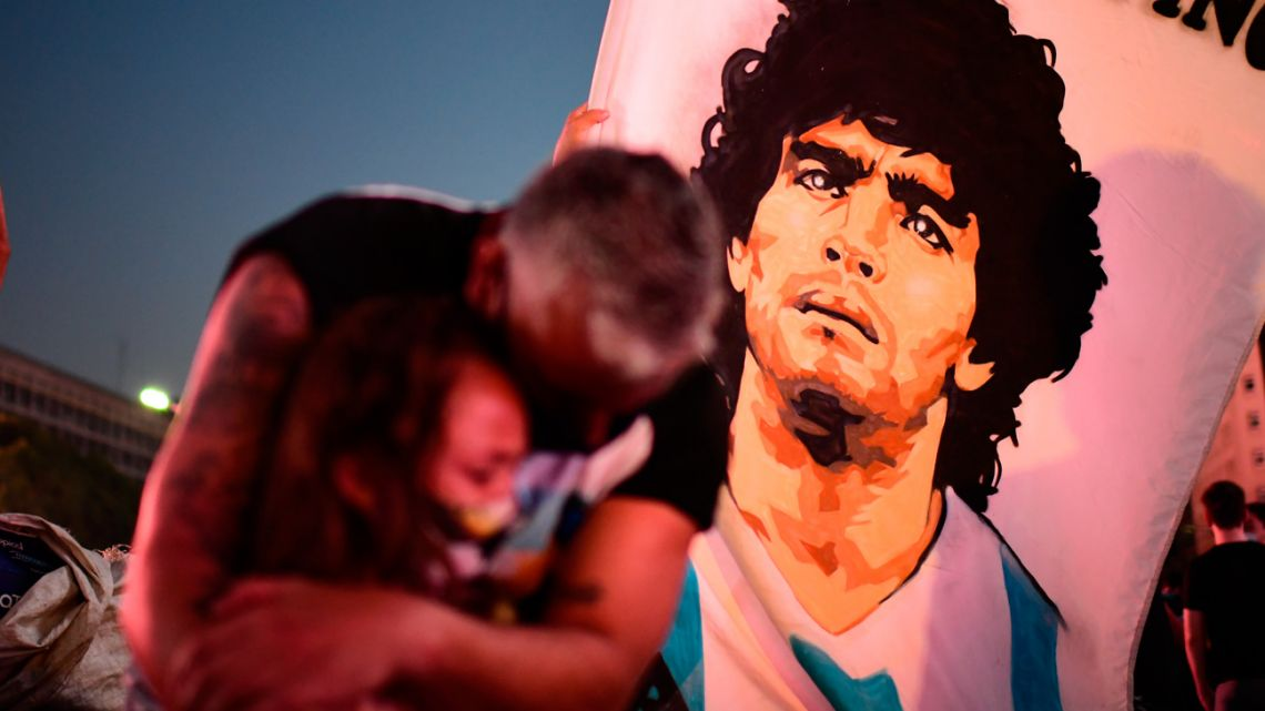 A father and her daughter, both fans of Diego Maradona, mourn as they gather by the Obelisk to pay homage on the day of his death in Buenos Aires, on November 25, 2020.