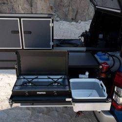 Funciona a gas e incluye un lavado plegable, un depósito de agua de 12 litros, conexión eléctrica de 12 V y una bandeja para los cubiertos.
