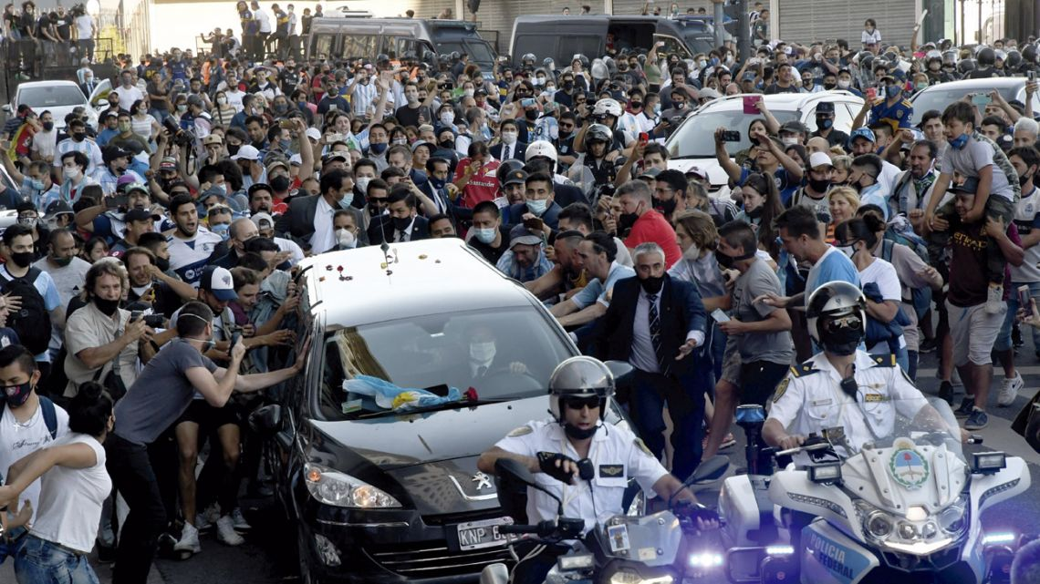 The hearse carrying Diego Maradona's funeral casket is mobbed as it departs the Casa Rosada for the cemetery.