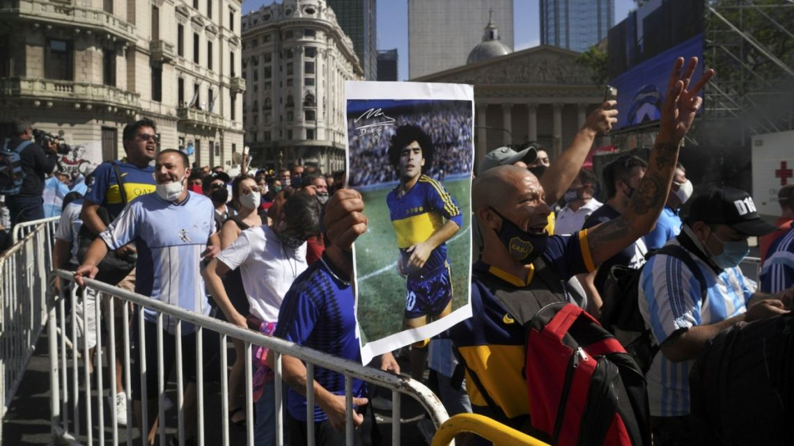 Fans queue outside the Casa Rosada, waiting to pay their respects to Diego Maradona.