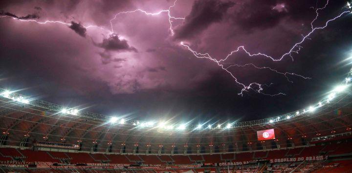 Un rayo chispas en el cielo en lo alto del estadio vacío Beira Rio en Porto Alegre, Brasil, antes del inicio del partido de fútbol a puerta cerrada de la Copa Libertadores entre el Internacional de Brasil y Boca Juniors.