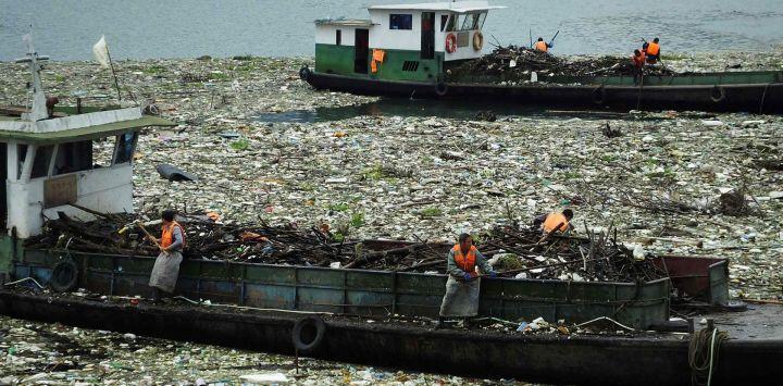 Los trabajadores retiran la basura del río Yangtze en Yichang, en la provincia de Hubei, en el centro de China.