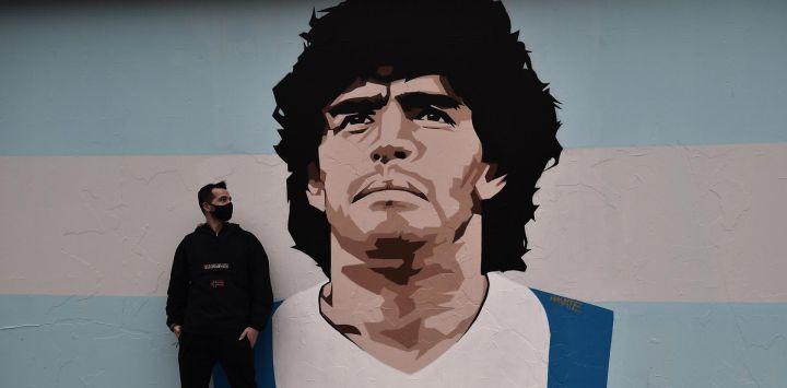 El artista callejero Stilos Ilias posa junto a su graffiti que representa a la leyenda del fútbol argentino Diego Maradona, pintado en una pared de una escuela primaria en el barrio de Kalamaria en Tesalónica.