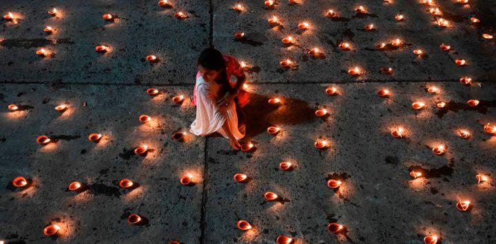 Un devoto hindú enciende lámparas de aceite tradicionales para celebrar Dev-Diwali a orillas del río sagrado Ganges en Calcuta.