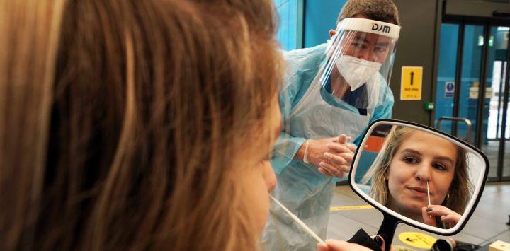 Inglaterra, Newcastle: la estudiante Amy Hariot Ingle, de 22 años, de la Universidad de Newcastle, realiza una autoprueba de Covid-19 mientras la administra David Black, un especialista en salud ocupacional, como parte de una prueba masiva de coronavirus en todo el Reino Unido, que comienza el martes.