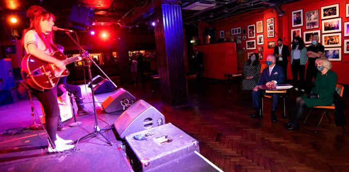 El Príncipe Carlos, Príncipe de Gales de Gran Bretaña y Camilla, Duquesa de Cornualles de Gran Bretaña aplauden después de una actuación musical de la cantante Emily Capell durante una visita al 100 Club para celebrar la economía nocturna en Londres.