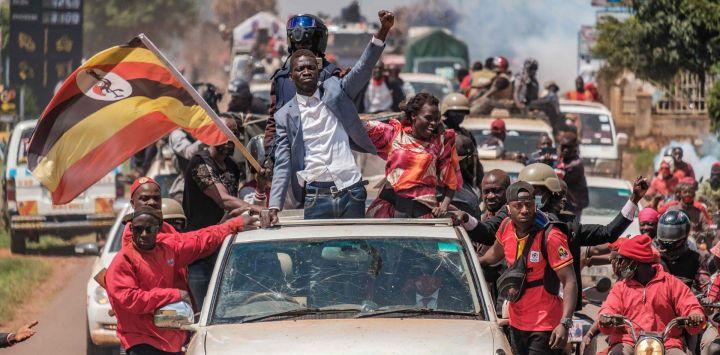El músico ugandés convertido en político Robert Kyagulanyi, también conocido como Bobi Wine, saluda a los partidarios mientras emprende su campaña hacia el este de Uganda, cerca de Kayunga.