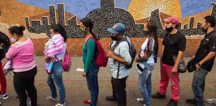 La gente hace fila para abordar un autobús junto a un mural que representa el edificio de la Asamblea Nacional, en Caracas antes de las elecciones parlamentarias en el país.