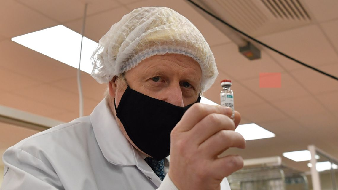 Britain's Prime Minister Boris Johnson, wearing a hair net and face covering, poses for a photograph with a vial.