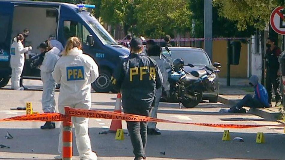 La policía trabajando en las pericias en el lugar donde fue asesinado el oficial González Sueiro. Sentado a un costado, el delincuente detenido.