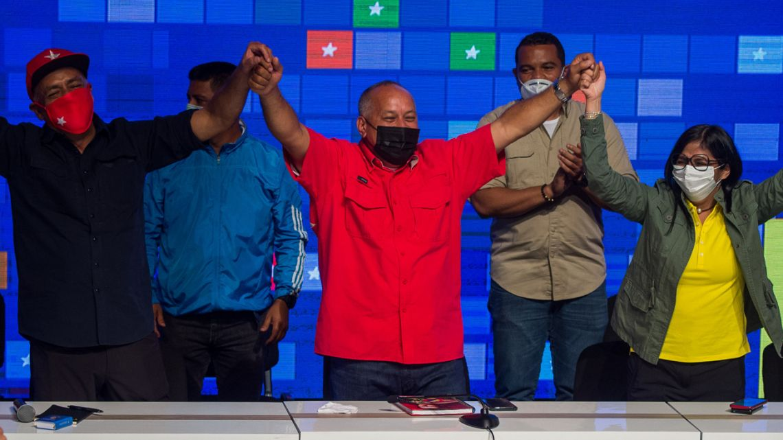 Socialist United Party of Venezuela (PSUV) leader Diosdado Cabello (centre) celebrates the legislative election results with Venezuela's Vice-President Delcy Rodríguez (right) and former communications minister Jorge Rodríguez (left) in Caracas on December 7, 2020.