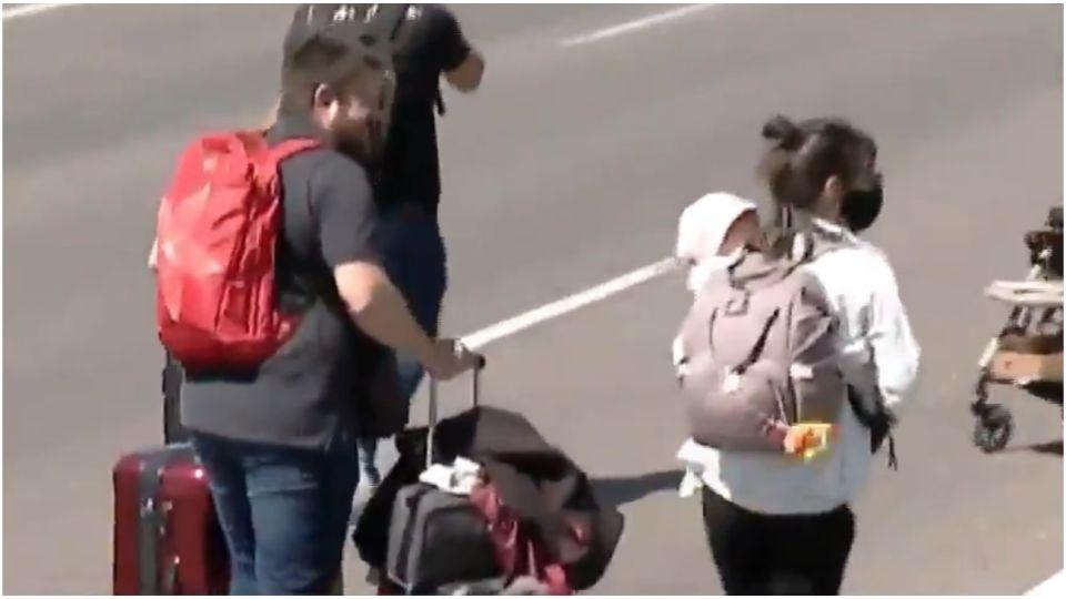 Pasajeros caminan por la autopista con niños en brazos y equipaje para no perder su vuelo.