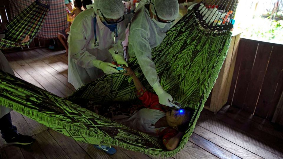 Personal sanitario atiende a un enfermo en una isla sobre el río Amazonas.