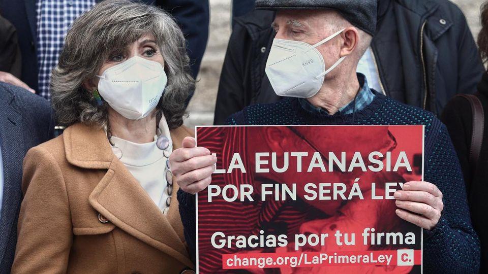 La exministra de Sanidad y actual secretaria de Sanidad de la Comisión Ejecutiva Federal del PSOE, María Luisa Carcedo (i), junto a Ángel Hernández (que ayudó a morir a su mujer, enferma de esclerosis múltiple) (d) celebran, frente al Congreso de los Diputados, la aprobación de la ley que regula la eutanasia, en Madrid (España), a 17 de diciembre de 2020. El Pleno del Congreso ha aprobado este jueves la Ley Orgánica para la regulación de la Eutanasia, con los únicos votos en contra de PP y Vox. El texto ha contado, así, con el apoyo del 56% de la Cámara (198 votos a favor, 138 en contra y dos abstenciones) y ahora continuará con su tramitación en el Senado.