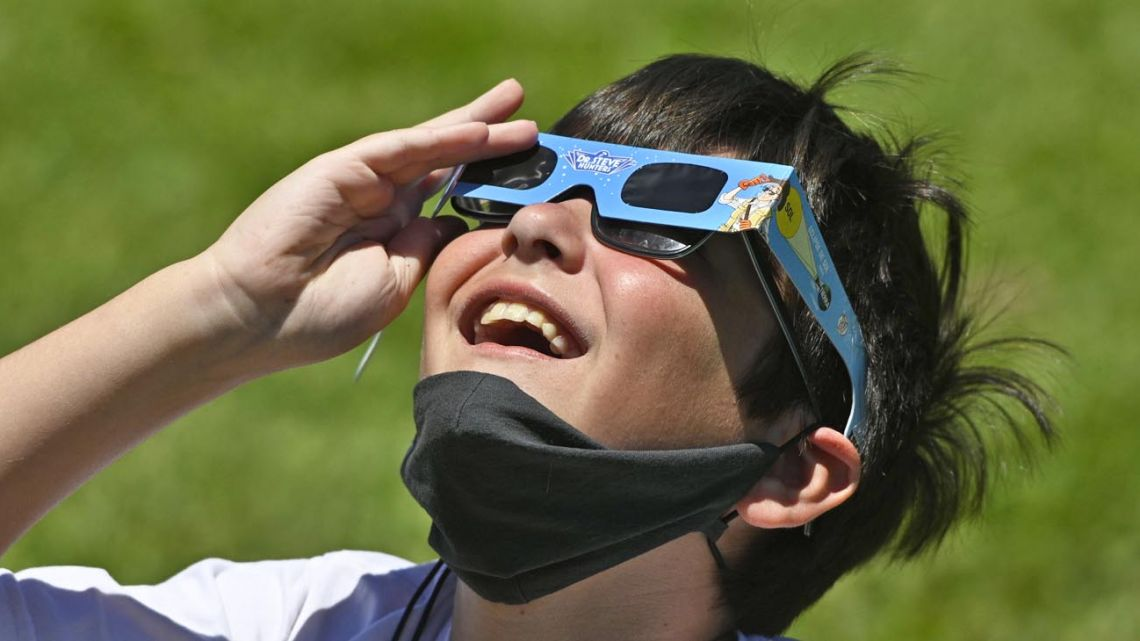 A boy using solar eclipse glasses.