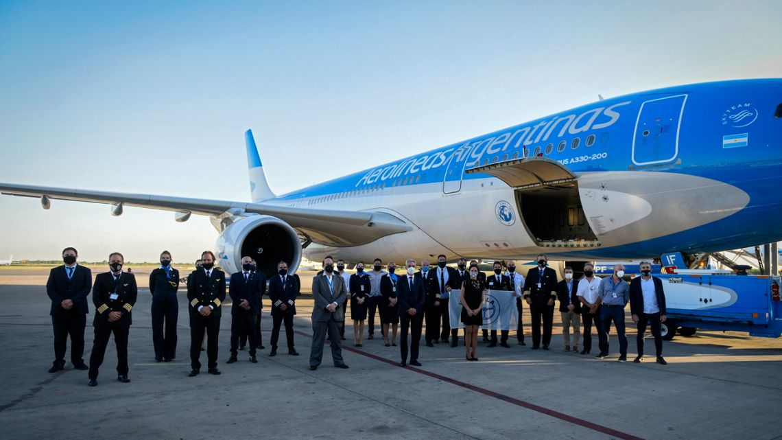 Crew members and authorities pose next to an Aerolineas Argentinas airplane before its departure to bring 300,000 doses of the Sputnik V vaccine against Covid-19 from Moscow, in Buenos Aires on December 22, 2020.