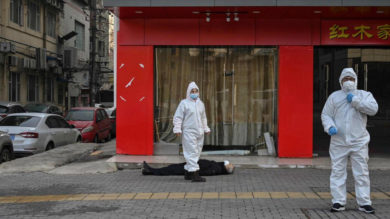 FOTO HISTÓRICA. Personal de emergencia revisa el cuerpo de un hombre que colapsó y murió en la calle en Wuhan el 26 de diciembre de 2019.