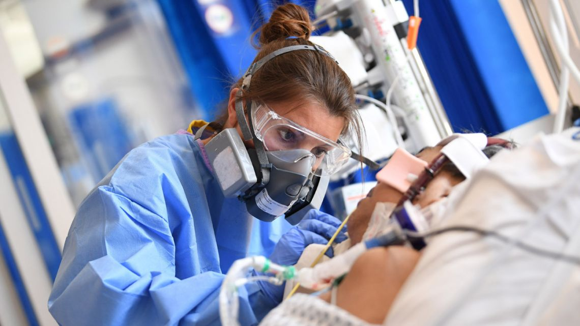 A member of the clinical staff wears personal protective equipment (PPE) as she cares for a patient at the Intensive Care unit at Royal Papworth Hospital in Cambridge, on May 5, 2020.