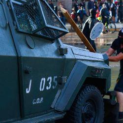 Chile, Santiago: un manifestante golpea un vehículo de policía blindado durante una manifestación para conmemorar el primer aniversario de la muerte de Mauricio Fredes, de 33 años, quien murió durante una manifestación. | Foto:Mauricio Méndez / Agencia Uno / DPA
