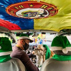 Un taxista se sienta junto a su elegante perro disfrazado de Papá Noel en Bogotá. | Foto:Juan Barreto / AFP