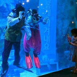 Buzos surcoreanos con vestidos tradicionales hanbok coreanos saludan a un niño en un acuario durante un evento para celebrar el Año Nuevo en el Lotte World Aquarium en Seúl. | Foto:Jung Yeon-je / AFP