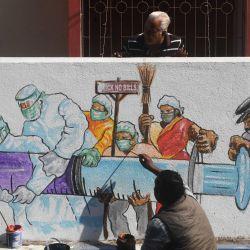 Los residentes miran mientras un artista da los toques finales a un mural que muestra a trabajadores de primera línea con una vacuna contra el coronavirus Covid-19 en Calcuta. | Foto:Dibyangshu Sarkar / AFP