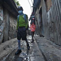 Bravin Ochieng, de 9 años, sale de su casa al amanecer en el barrio pobre de Mathare mientras se dirige a la escuela con su madre, Rita Adhiambo, caminando de cerca detrás de él en Nairobi, Kenia, mientras los estudiantes regresan a la escuela. tras un cierre de nueve meses ordenado por el gobierno en marzo de 2020 para frenar la propagación del coronavirus COVID-19. | Foto:Tony Karumba / AFP
