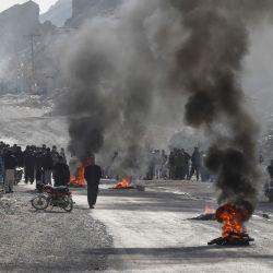 Miembros de la comunidad chiíta Hazara queman neumáticos durante una protesta tras el asesinato de 11 trabajadores de su comunidad, en Quetta. | Foto:Banaras Khan / AFP