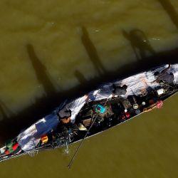 Hombres colocan una red en un barco de pesca en el río Bassac en Phnom Penh. | Foto:Tang Chhin Sothy / AFP