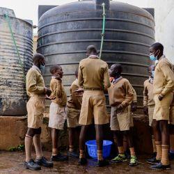 Los estudiantes de la escuela primaria Ayany llenan un recipiente con agua para limpiar el aula antes de la clase en la mañana del día oficial de reapertura de las escuelas públicas, en el barrio marginal de Kibera, Kenia, cuando los estudiantes regresan a la escuela después de nueve meses. | Foto:Gordwin Odhiambo / AFP