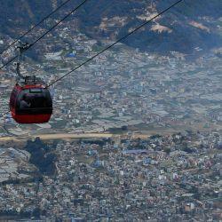 Los pasajeros viajan en un teleférico en la cima de la colina Chandagiri en medio de condiciones de niebla tóxica en Katmandú. | Foto:Prakash Mathema / AFP