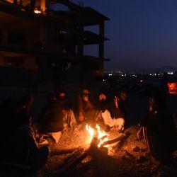 Los dolientes de una comunidad chiíta hazara se calientan alrededor de un fuego cerca de los ataúdes de los mineros que murieron en un ataque de hombres armados en el área montañosa de Machh, durante una sentada de protesta en el bypass oriental, en las afueras de Quetta. | Foto:Banaras Khan / AFP