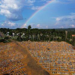Vista aérea del cementerio reservado para las víctimas de la pandemia de COVID con un arco iris en el cielo en el cementerio de Nossa Senhora Aparecida en Manaus, en la selva amazónica de Brasil. | Foto:Michael Dantas / AFP