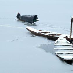 Un barquero usa un remo para romper la capa de hielo de la parte congelada del lago Dal después de las fuertes nevadas en Srinagar. | Foto:Tauseef Mustafa / AFP
