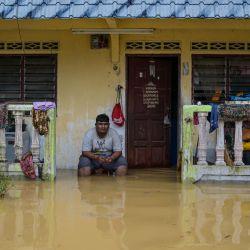 Un residente se sienta afuera de su casa, parcialmente sumergido en las inundaciones, en Kuala Kaung, cerca de Lanchang, en el estado de Pahang, en Malasia. | Foto:Mohd Rasfan / AFP