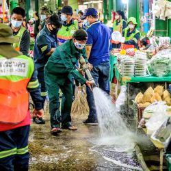 Los empleados de la Autoridad Metropolitana de Bangkok limpian y desinfectan el mercado de flores de Yodpiman en Bangkok, después de que el gobierno impusiera más restricciones debido al reciente brote de coronavirus Covid-19. | Foto:Mladen Antonov / AFP