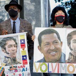 Simpatizantes del gobierno venezolano liderado por el presidente Nicolás Maduro sostienen carteles celebrando el nuevo parlamento venezolano, frente a la Asamblea Nacional, en Caracas. | Foto:Pedro Rances Mattey / AFP