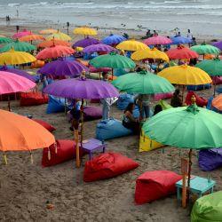 La gente visita la playa de Seminyak cerca de Denpasar, en la isla turística de Bali, en Indonesia. | Foto:Sonny Tumbelaka / AFP