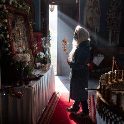 Los fieles rezan a un ícono cuando salen después de un servicio de la liturgia de la Natividad de Cristo en la Iglesia Ortodoxa Serbia del Santo Príncipe Lazar en Bournville, Birmingham, Inglaterra. | Foto:Oli Scarff / AFP