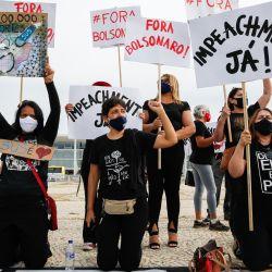 La gente protesta en honor a las doscientas mil personas muertas por la enfermedad del coronavirus, COVID-19, exigiendo una vacuna y contra el presidente brasileño Jair Bolsonaro, frente al Palacio Planalto en Brasilia. | Foto:Sergio Lima / AFP