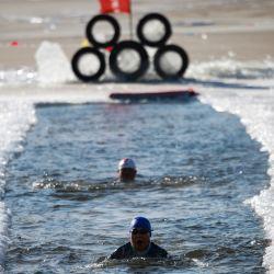 Dos nadadores de invierno nadan en una piscina cortada en un lago congelado en Shenyang, en la provincia nororiental de Liaoning. | Foto:STR / AFP