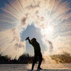 Una mujer arroja agua caliente al aire, que instantáneamente se condensa en cristales de hielo en medio de temperaturas de menos 27 grados Celsius, en Shenyang, en la provincia de Liaoning, en el noreste de China. | Foto:STR / AFP