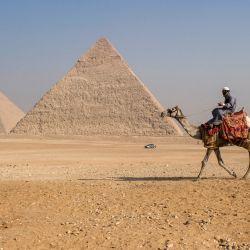 Un entrenador de camellos monta un camello cerca de la Gran Pirámide de Keops y la Pirámide de Khafra en la Necrópolis de las Pirámides de Giza en las afueras occidentales de la ciudad gemela de Giza, la capital egipcia. | Foto:Amir Makar / AFP