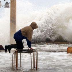 España, Málaga: una persona se encuentra en una mesa sobre los muebles de una terraza con vistas a las inundaciones provocadas por la tormenta Filomena. | Foto:Álex Zea / EUROPA PRESS / DPA