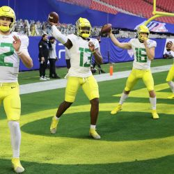 Los mariscales de campo Tyler Shough, Anthony Brown y Bradley Yaffe de los Oregon Ducks calientan antes del PlayStation Fiesta Bowl contra los Iowa State Cyclones en State Farm Stadium en Glendale, Arizona. | Foto:Christian Petersen / Getty Images / AFP
