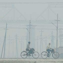 Hombres andan en bicicleta en medio de la niebla en Allahabad. | Foto:Sanjay Kanojia / AFP