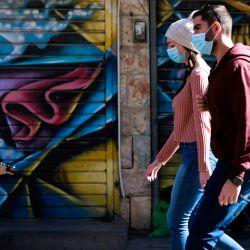 Una pareja, con máscaras protectoras debido a la pandemia de COVID-19, pasa junto a un guitarrista en el mercado de Mahane Yehuda en Jerusalén. | Foto:Menahem Kahana / AFP