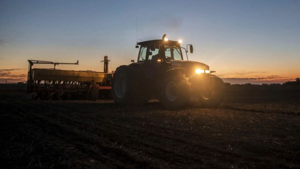 A farmer ploughs a field as the sun sets to prepare for corn planting in Rojas, Buenos Aires Province.