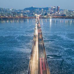 La foto muestra una vista general del tráfico que pasa por un puente sobre el río Han congelado, antes del horizonte de la ciudad de Seúl. | Foto:Ed Jones / AFP