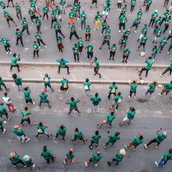 La gente calienta antes de participar en la vigésima edición de Great Ethiopian Run, en Addis Abeba. - La carrera se pospuso 8 semanas desde su fecha original debido a la pandemia Covid-19. | Foto:EDUARDO SOTERAS / AFP